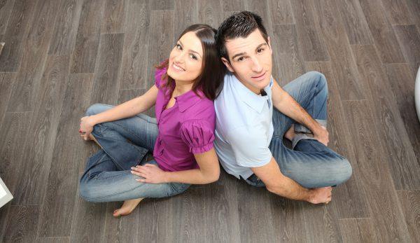 Couple Sat Back To Back On Laminate Flooring