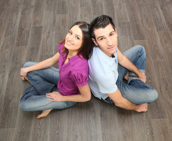 Couple Sat Back To Back On Laminate Flooring